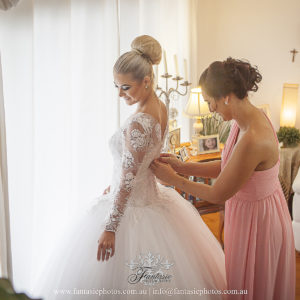 Beautiful bride and maid of honor getting ready at home