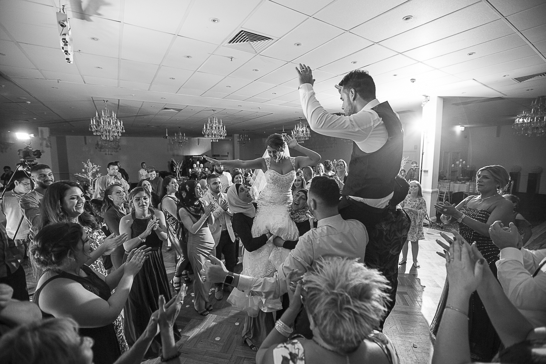 Wedding guests lifted up bride and groom celebrating during the dance on dance floor | Fantasie Photography