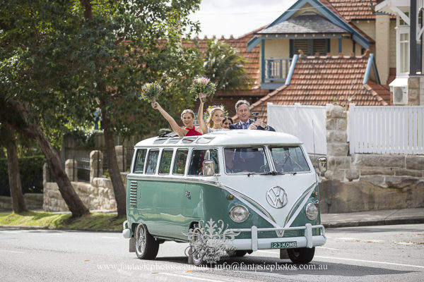 Bride and bridesmaid driving volkswagen kombi to wedding ceremony