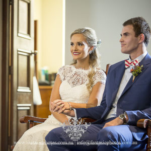 Beautiful Bride and Groom sitting and holding hands in ceremony at Blessed Sacrement Mosman