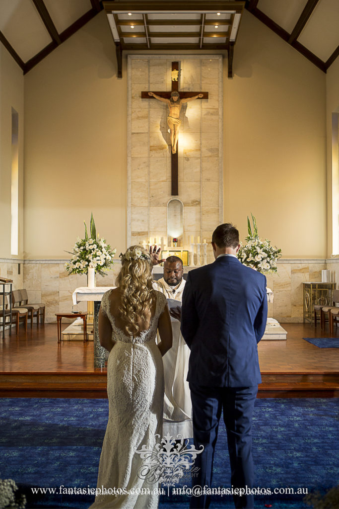 Bride and groom vowing in front of priest